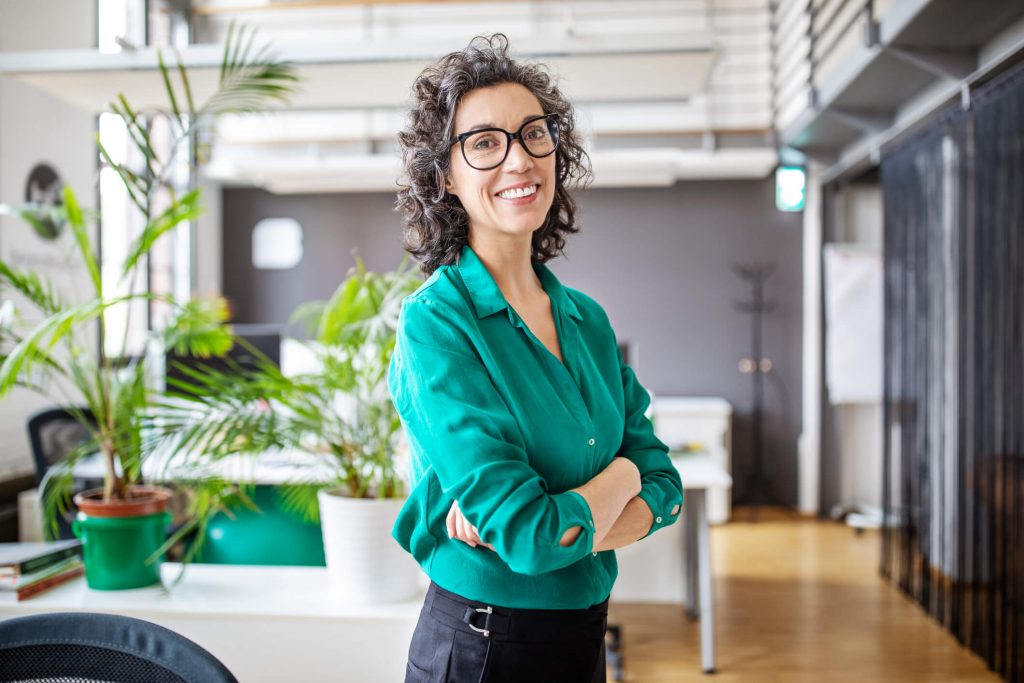 A woman with curly, graying hair standing in a sunny office wearing a green blouse and crossing her ams while smiling